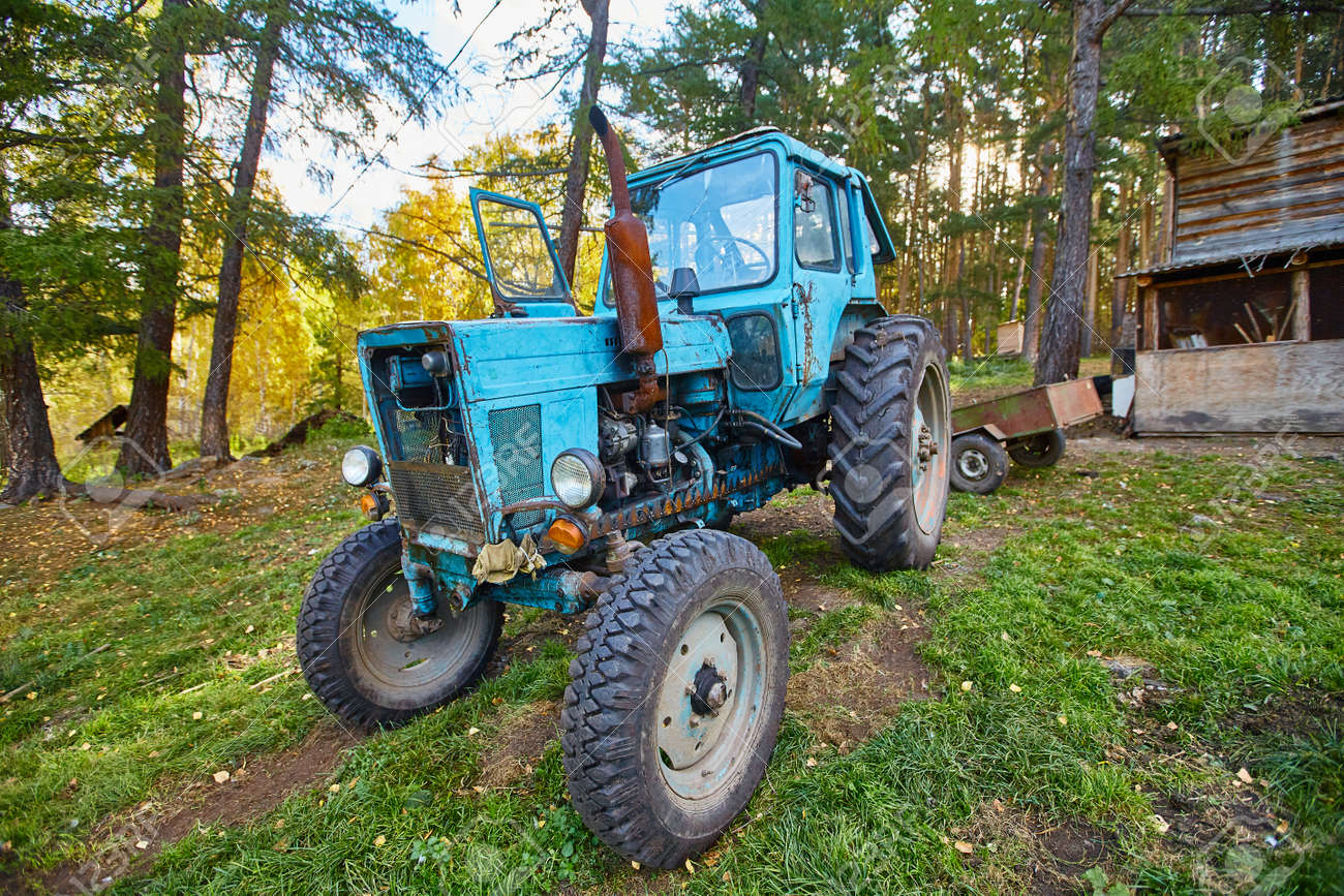 An old blue tractor stands in a farmyard. - 158639771