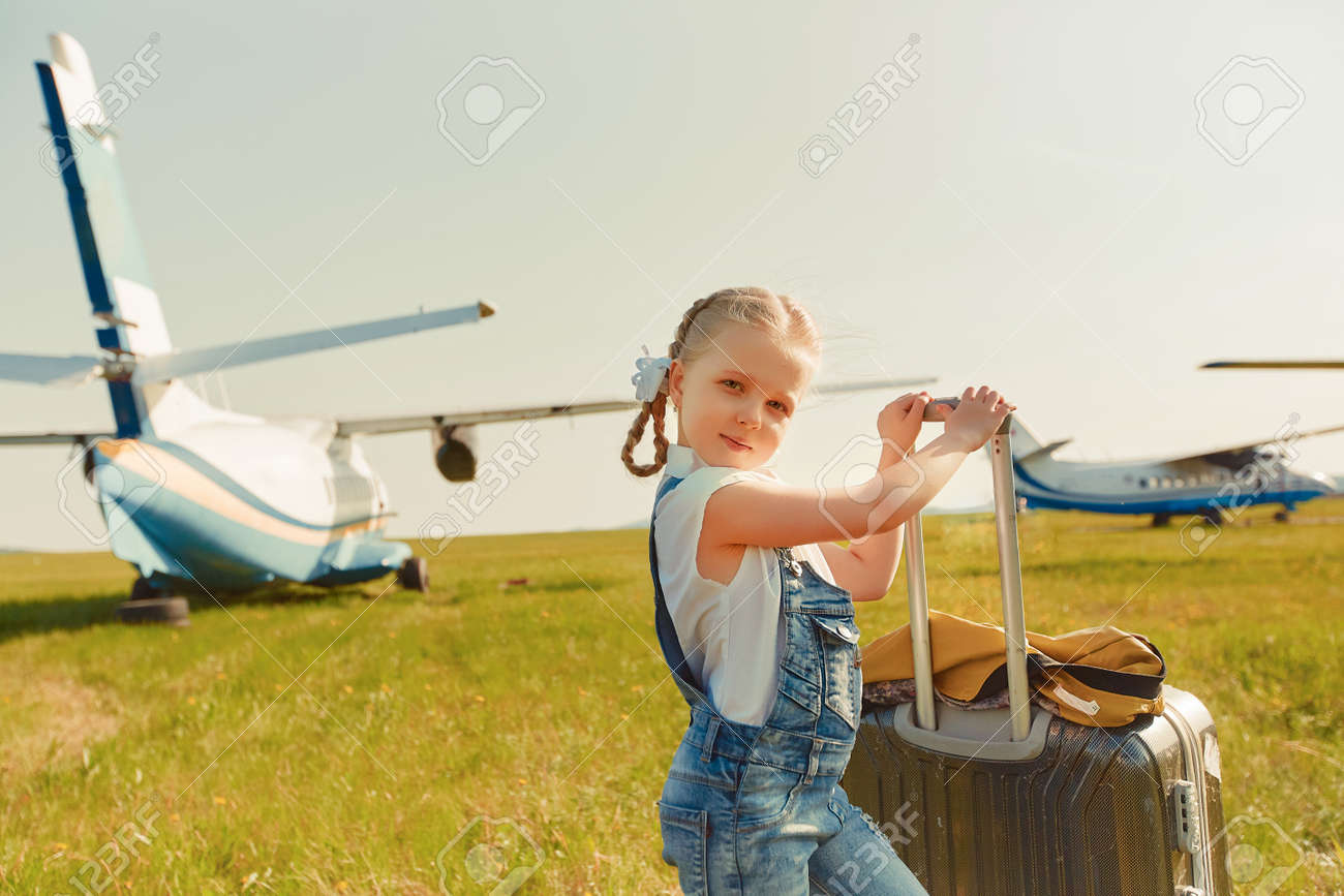 A little girl with a suitcase on the tarmac is going to travel by plane. - 158561424