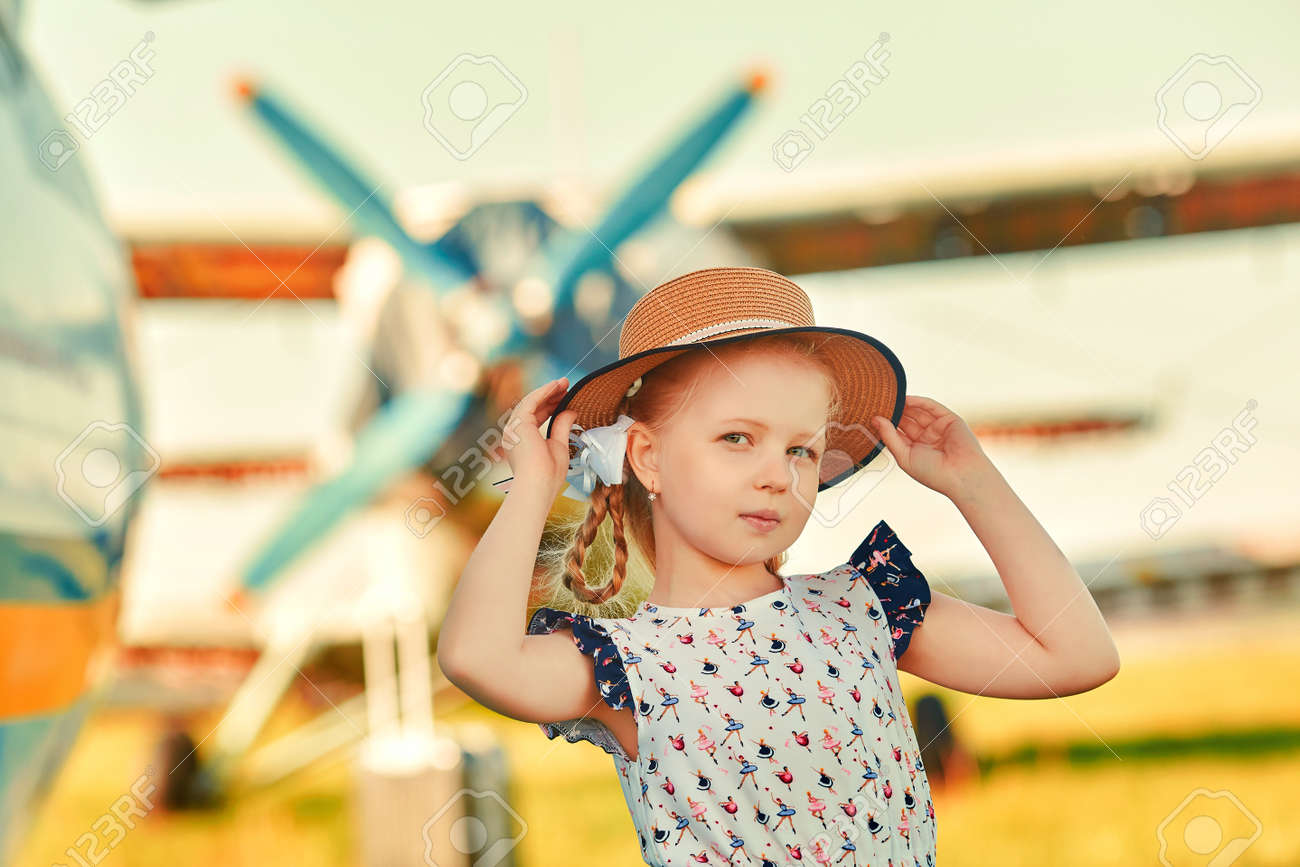 A cute child in a romantic hat stands on the tarmac, aircraft propellers in the background. The concept of dreams about traveling - 158561737