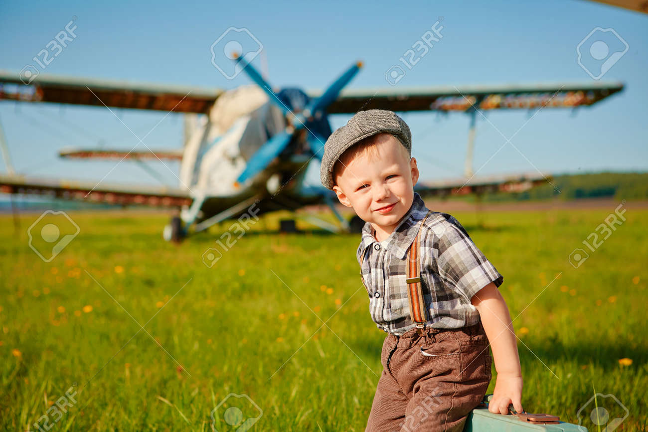 A little boy with a small suitcase on the airfield. - 158609321