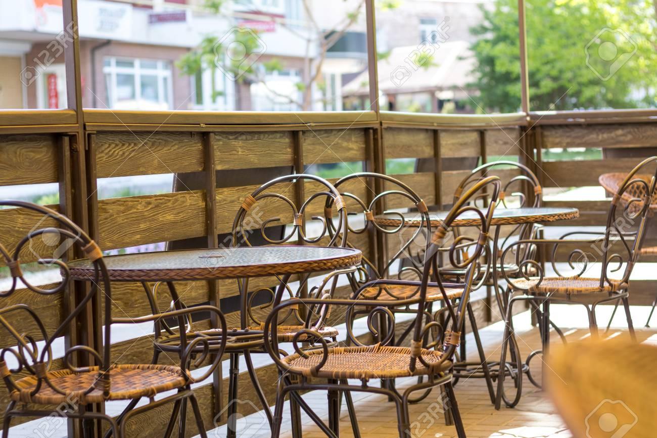 Acogedora Terraza De La Cafetería De Verano Con Mesas Y Sillas De Mimbre