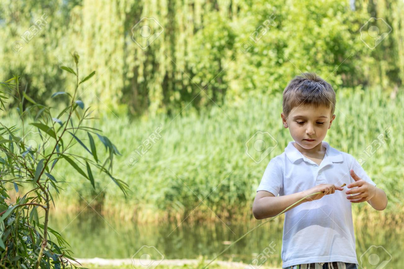 Happy little boy playing at the pond in the city park on a summer sunny day. Close up. Beautiful summer background with copy space Stock Photo - 92953513