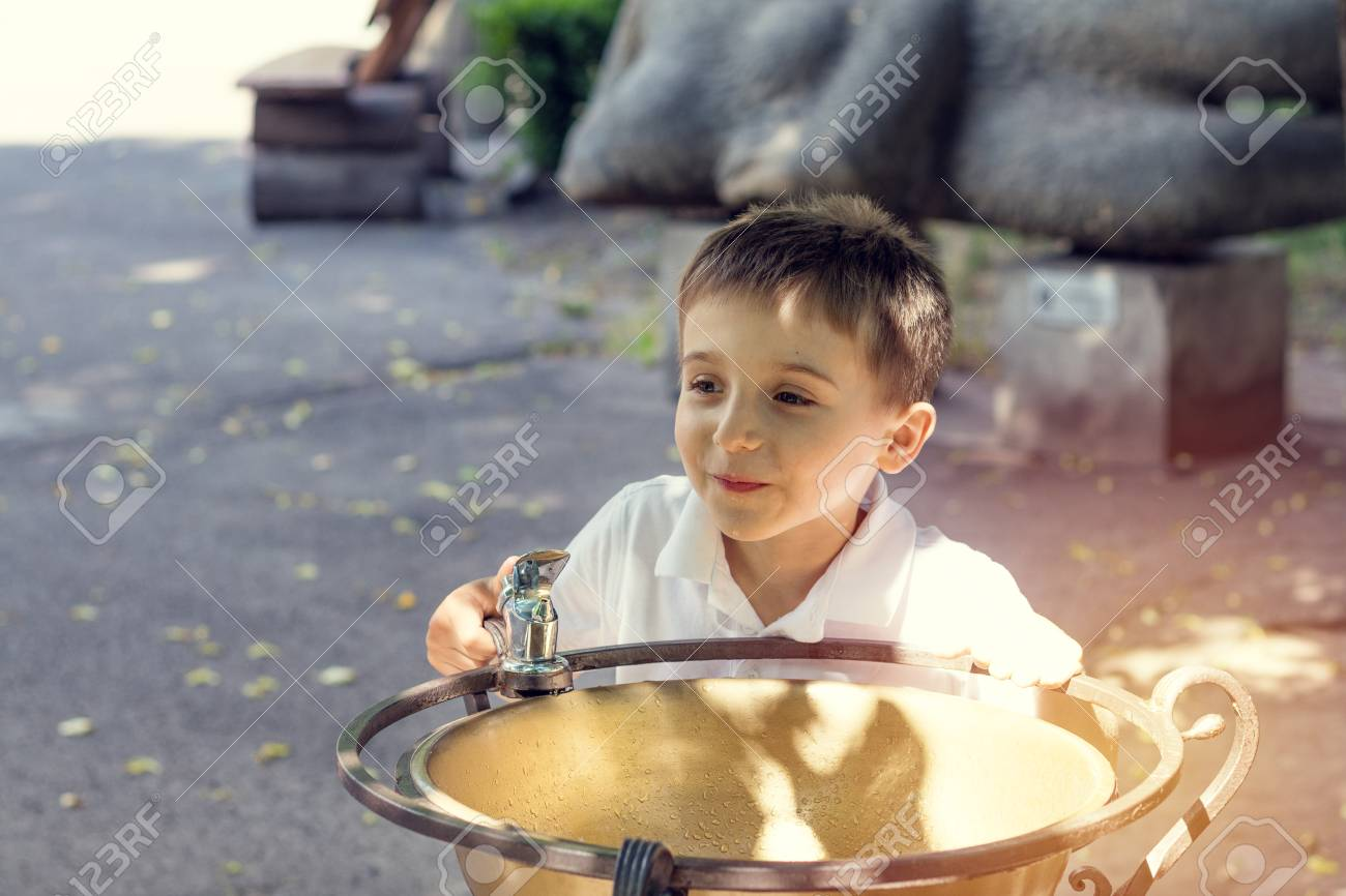 Happy little boy drinking water from fountain in the city park on a summer sunny day. Close up. Beautiful summer background with copy space Stock Photo - 92953527