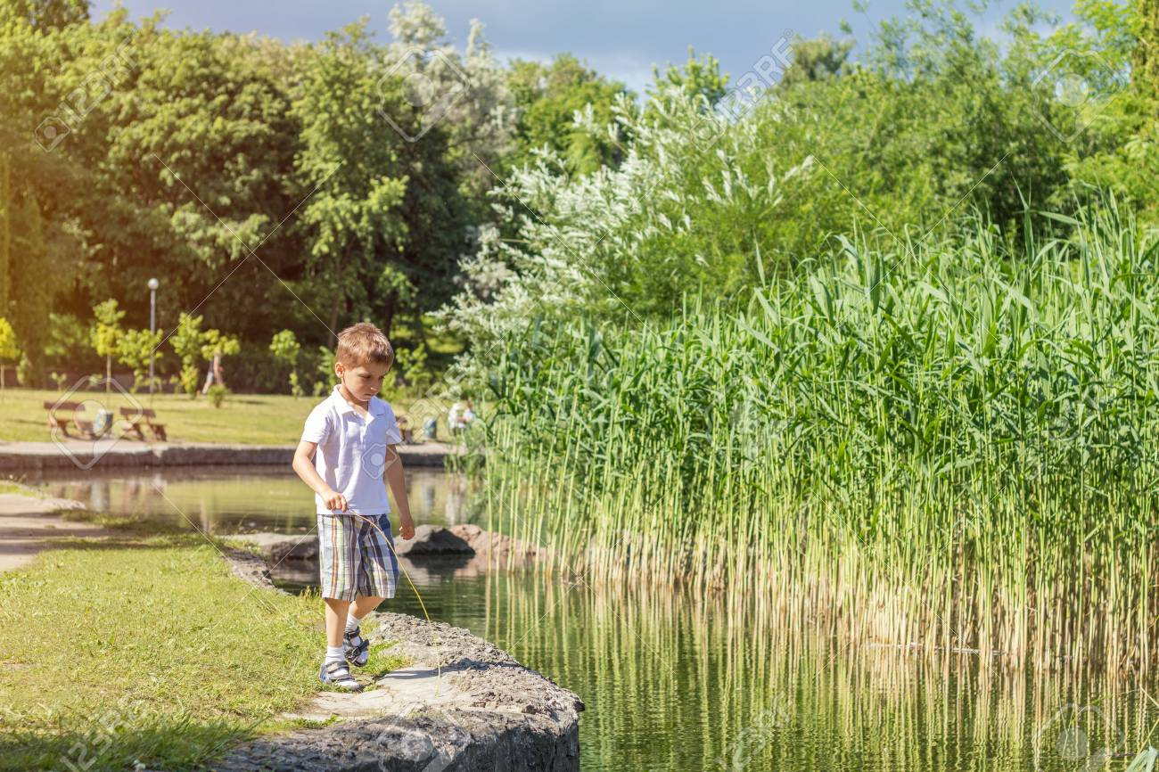 Happy little boy playing at the pond in the city park on a summer sunny day. Close up. Beautiful summer background with copy space Stock Photo - 92908857