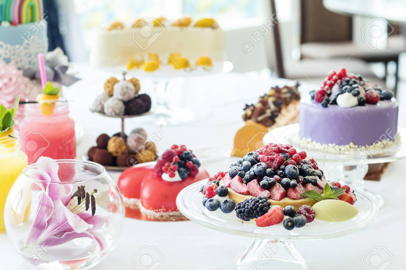 Many sweet pastries on white table with fresh summer berries. Festive table settings. Light background. Shallow depth of field Stock Photo - 92991258