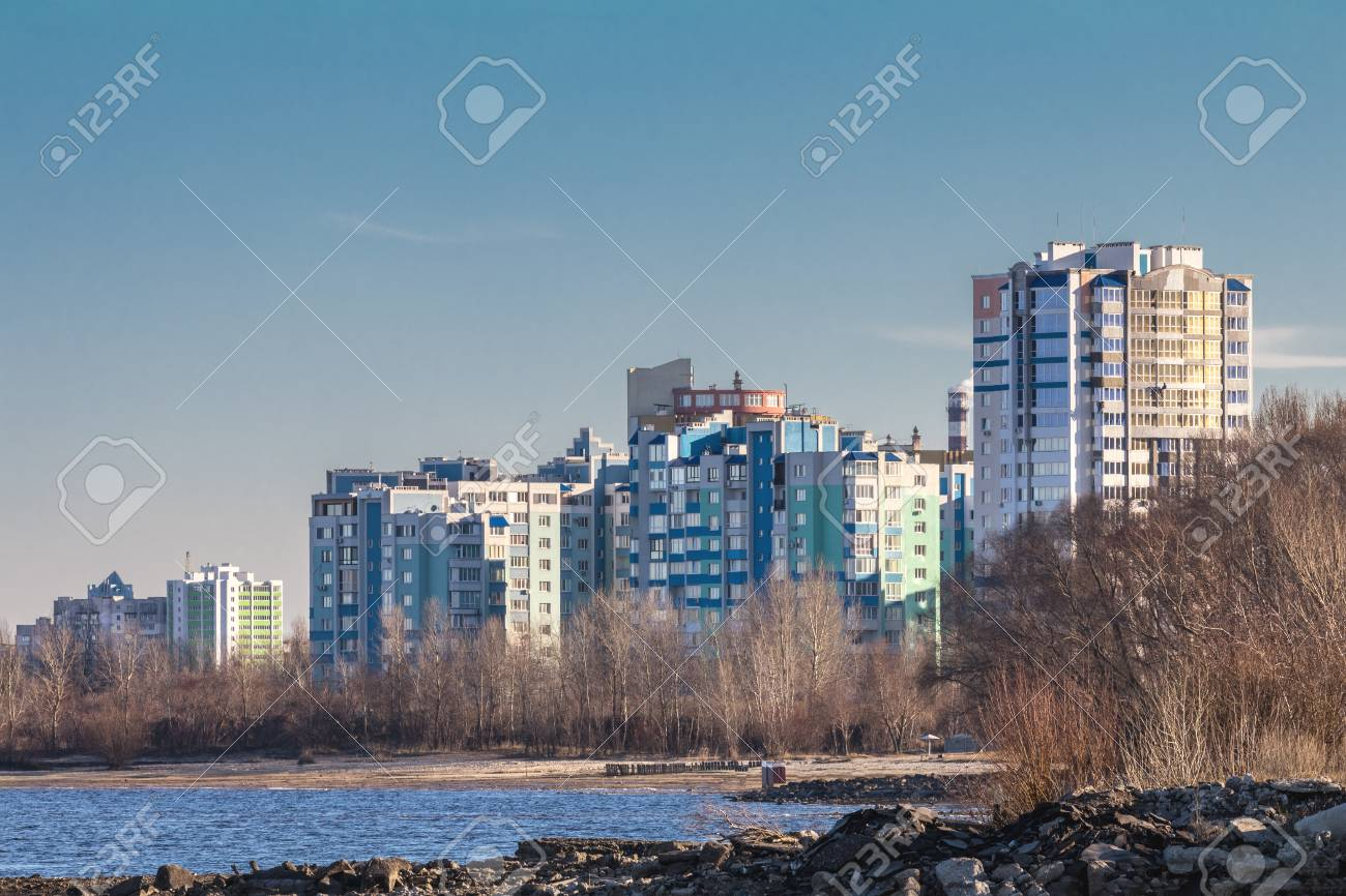 Cityscapes and skyline in clear blue sky on view from river. Sunny autumn day on city beach near river. Stock Photo - 93195698