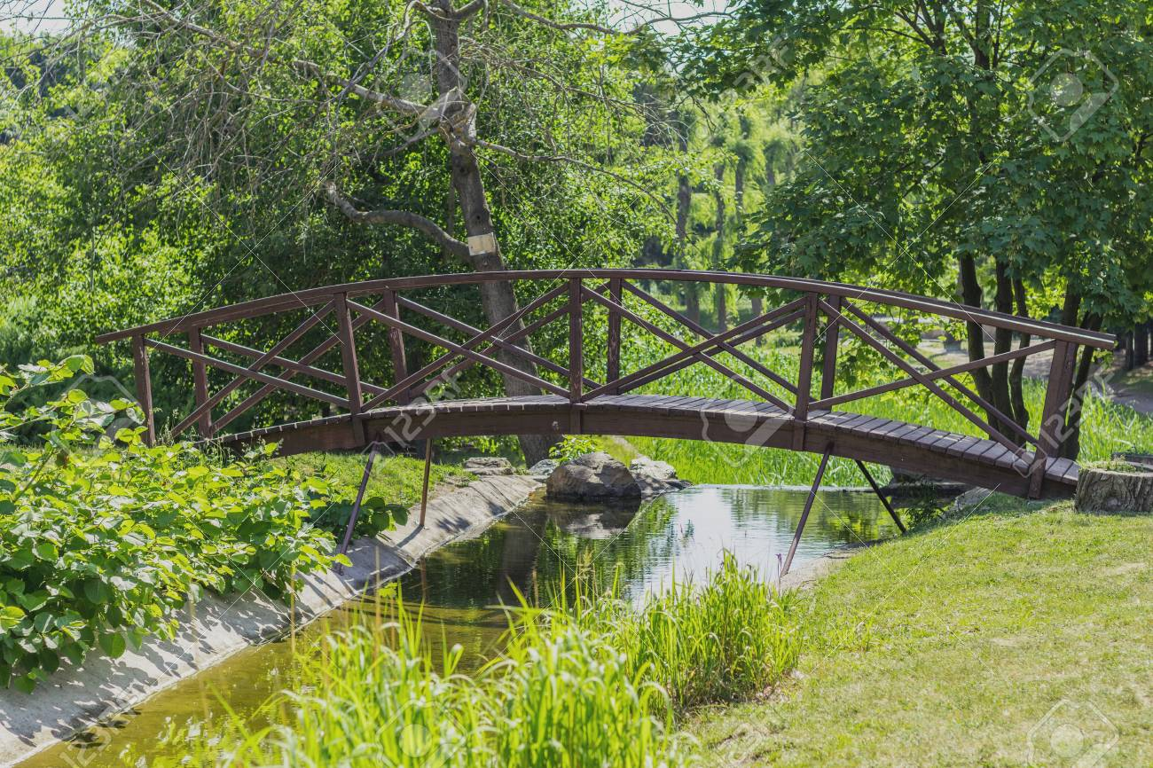 Summer footpath in the city park with a bridge on a sunny day Stock Photo - 93154224
