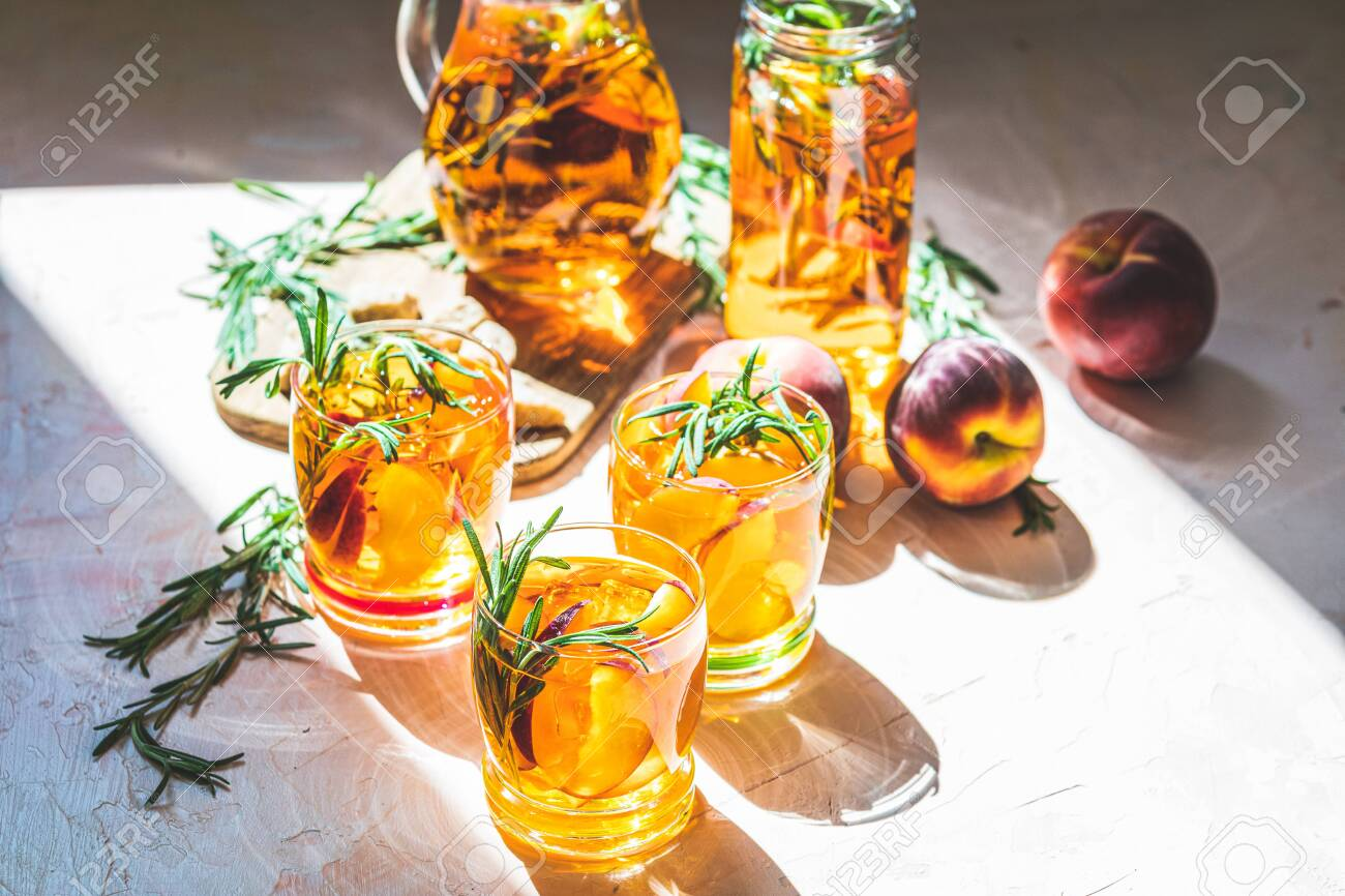 Glasses of sweet peach iced tea, Summer cold peach fizz cocktail with rosemary. Sunny light. - 128302402