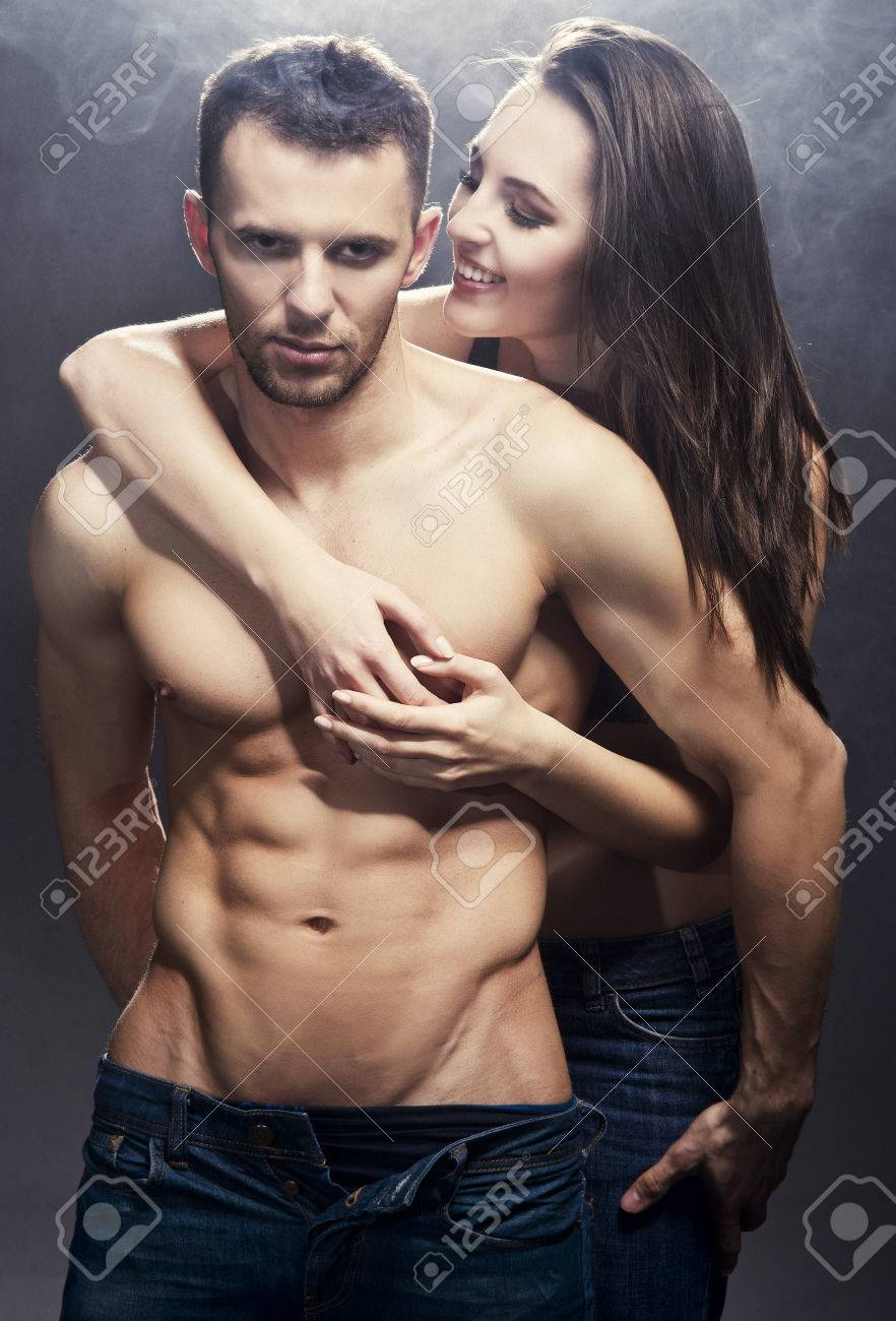 Beautiful young smiling couple in love embracing indoor Stock Photo - 25634773