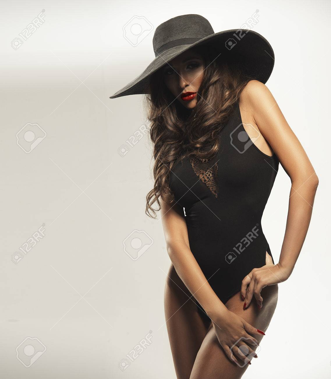 460b84febea Beautiful young woman with red lips wearing summer black hat with large  brim Stock Photo -
