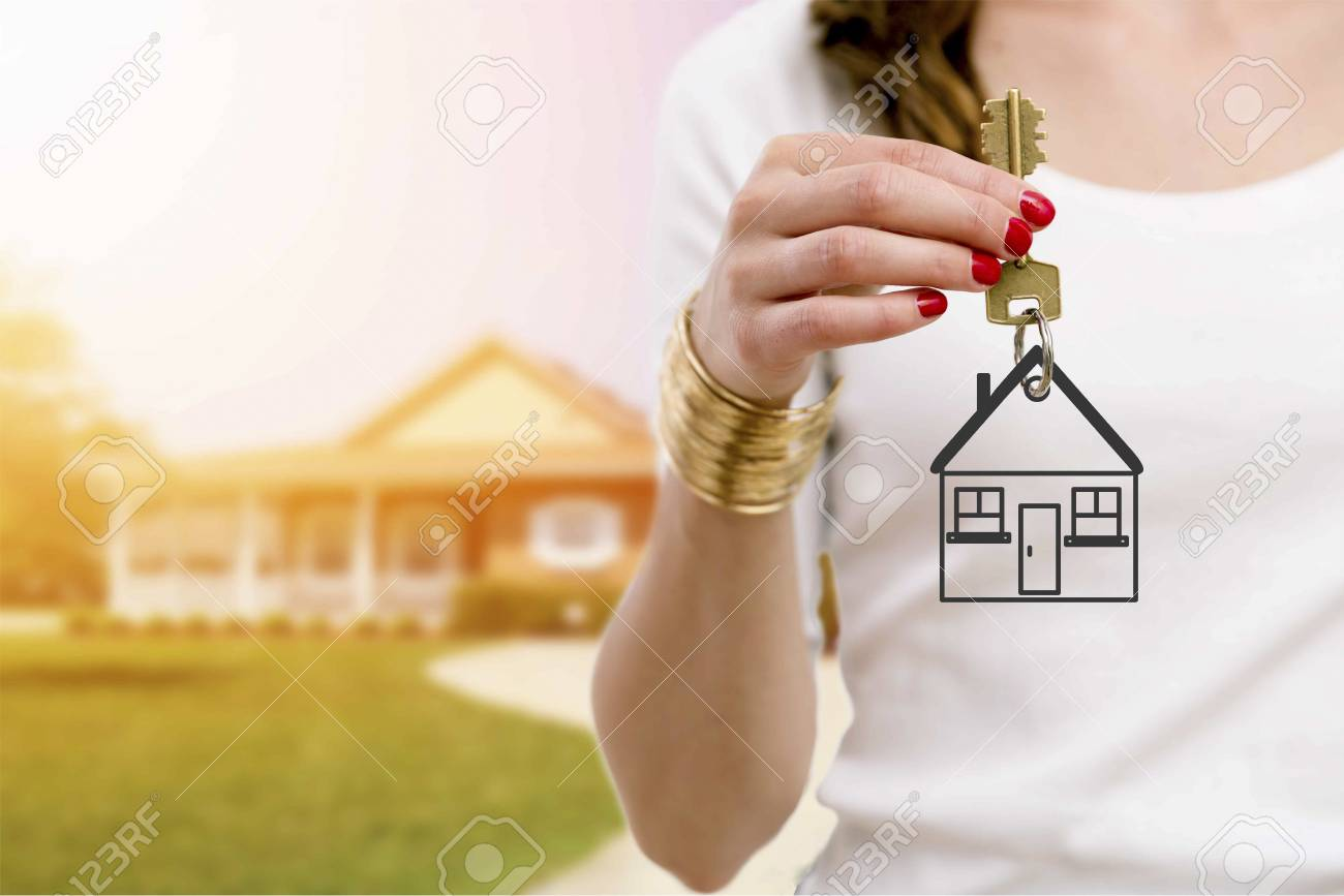 Real estate agent holding keys in front of a beautiful new home. - 89305220
