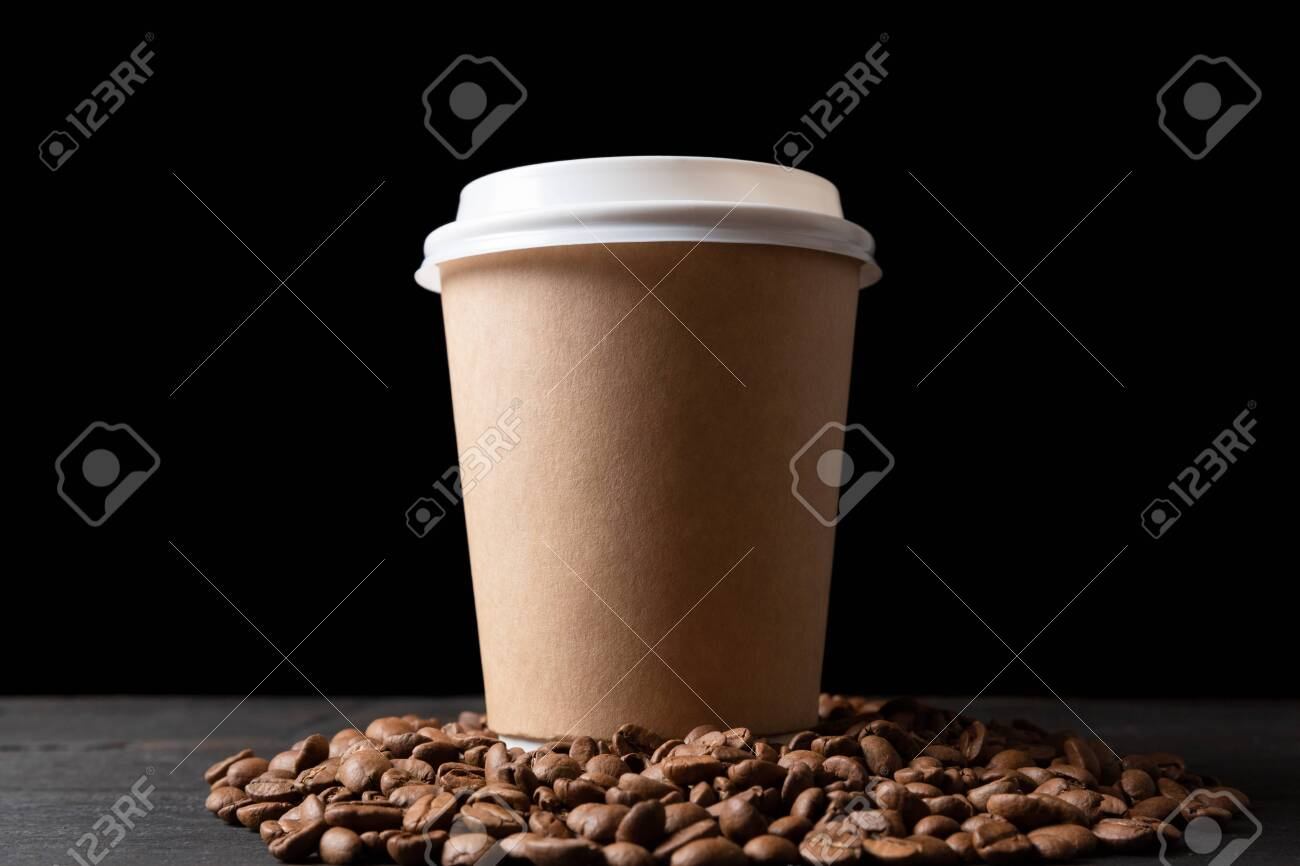 Paper cup of coffee and coffee beans on dark wooden table. Good quality coffee - 131605984