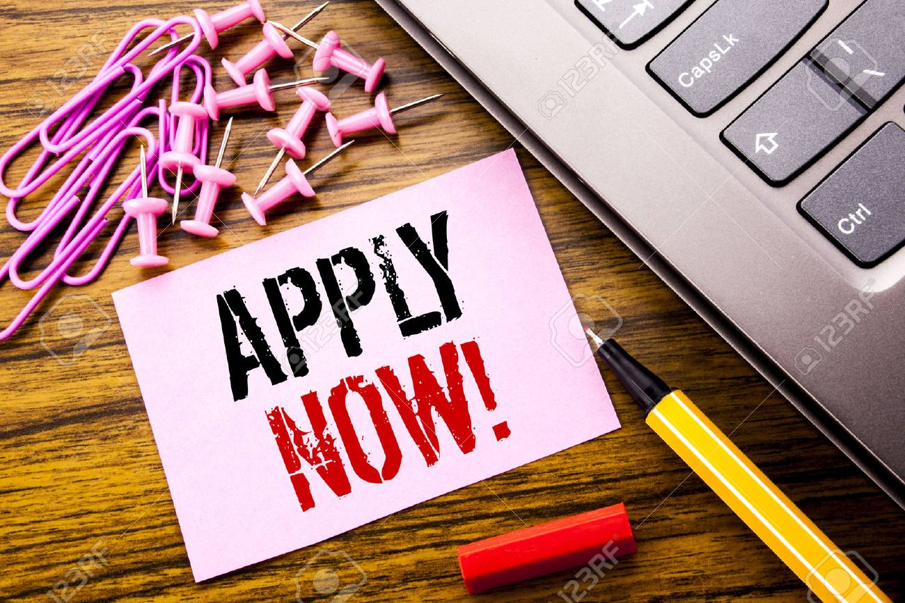 Handwritten text showing Apply Now. Business concept for Job Hiring Application written on pink sticky note paper on wooden background next to keyboard. With red pen. - 96174673