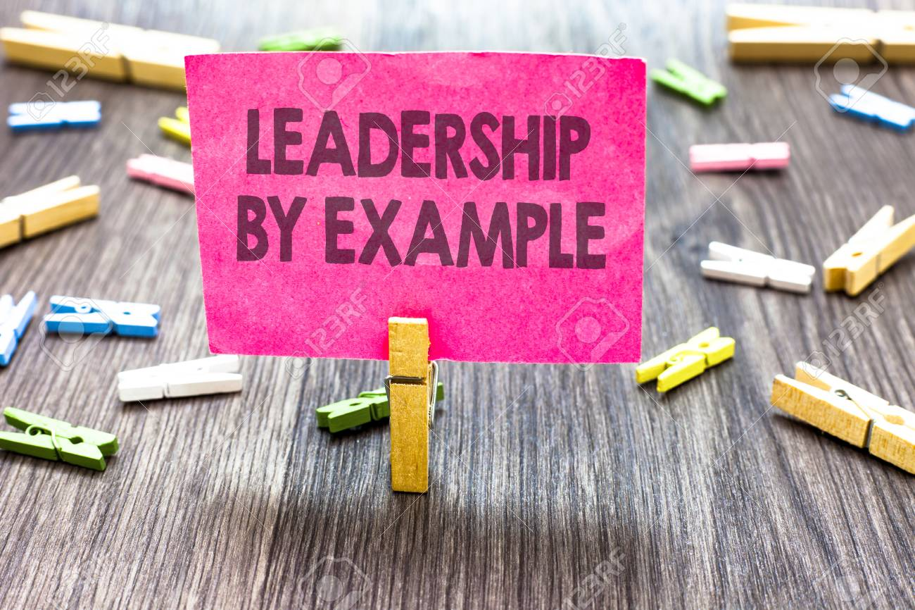 Writing note showing Leadership By Example. Business photo showcasing Becoming role model for people Have great qualities Multiple clips woody table small card clipped notice announcement - 104561309