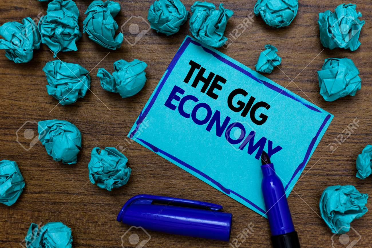 Conceptual hand writing showing The Gig Economy. Business photo showcasing Market of Short-term contracts freelance work temporary written blue letters on page blue marker and paper lumps - 105531451