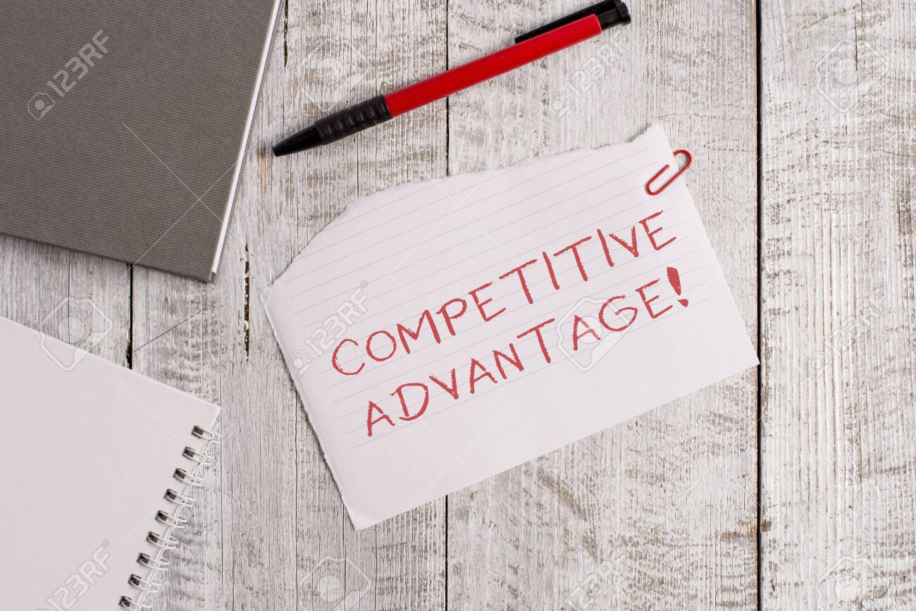 Handwriting text Competitive Advantage. Conceptual photo Company Edge over another Favorable Business Position Torn paper and notebook sheet with a pen placed on top of wooden table - 124384723