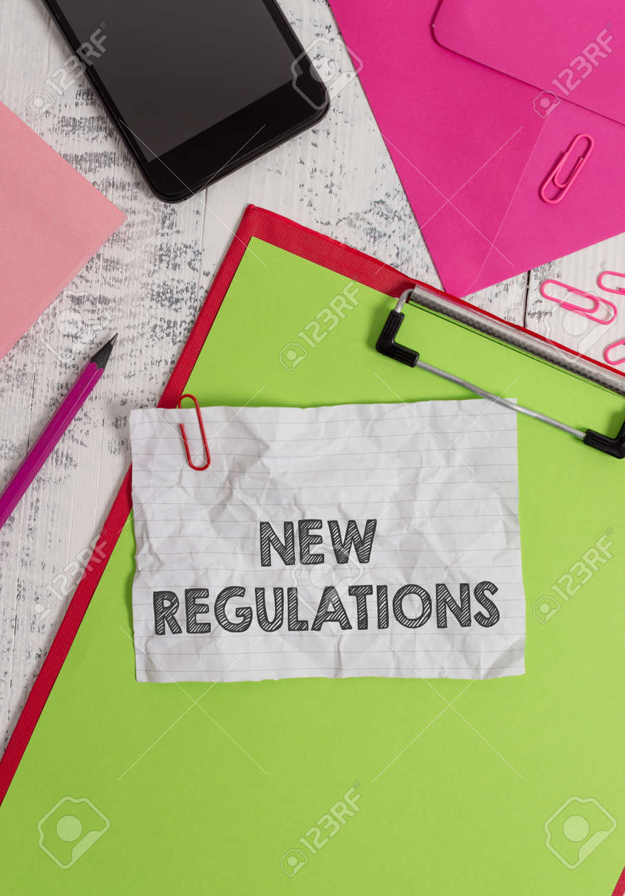Conceptual hand writing showing New Regulations. Concept meaning Regulation controlling the activity usually used by rules. Clipboard sheet pencil smartphone clips notepad wooden back - 126246316