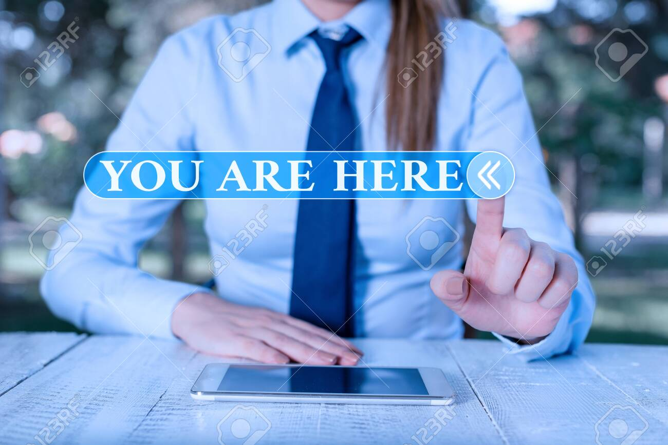 Handwriting text You Are Here. Conceptual photo This is your location reference point global positioning system Female business person sitting by table and holding mobile phone - 134496777