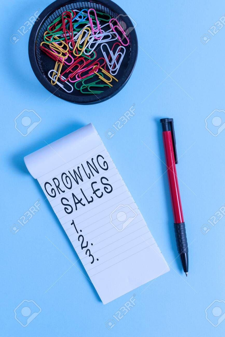 Conceptual hand writing showing Growing Sales. Concept meaning Average sales volume of a company products has grown Notebook and stationary with mouse above pastel backdrop - 142829328