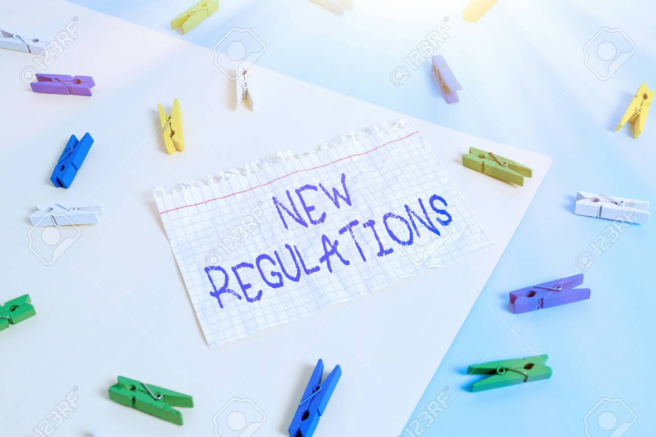 Word writing text New Regulations. Business photo showcasing Regulation controlling the activity usually used by rules. Colored clothespin paper empty reminder yellow blue floor background office - 146076549