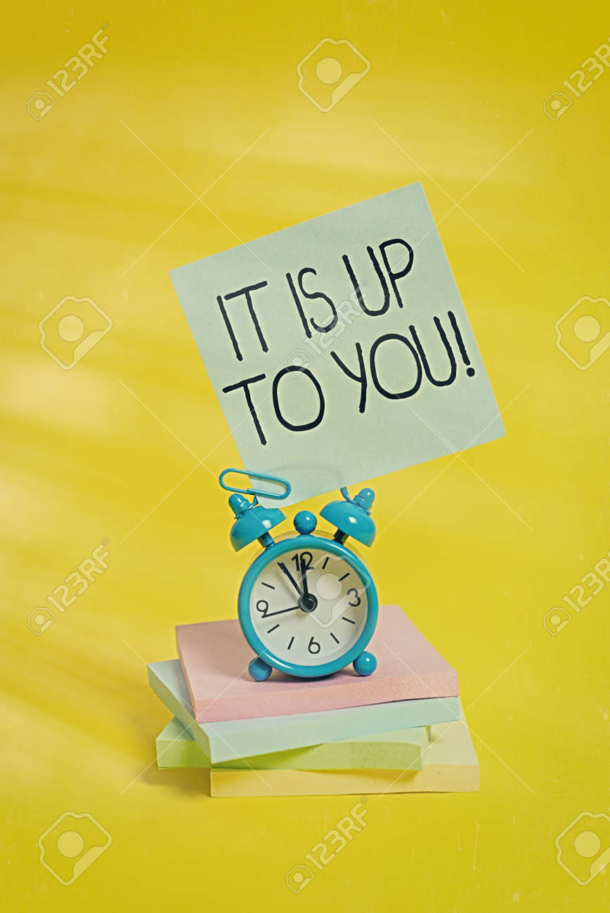 Handwriting text It Is Up To You. Conceptual photo Used to tell an individual that they are the one to decide Metal alarm clock blank sticky note stacked notepads colored background - 149000176