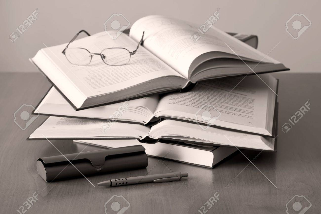 opened books pen and glasses on sepia background - 8512575