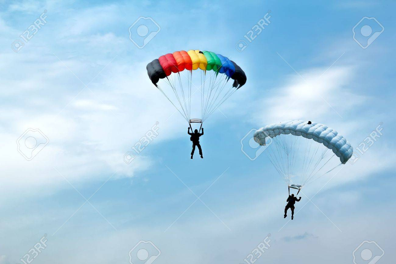 two silhouettes of unidentified skydivers on blue sky - 17576773
