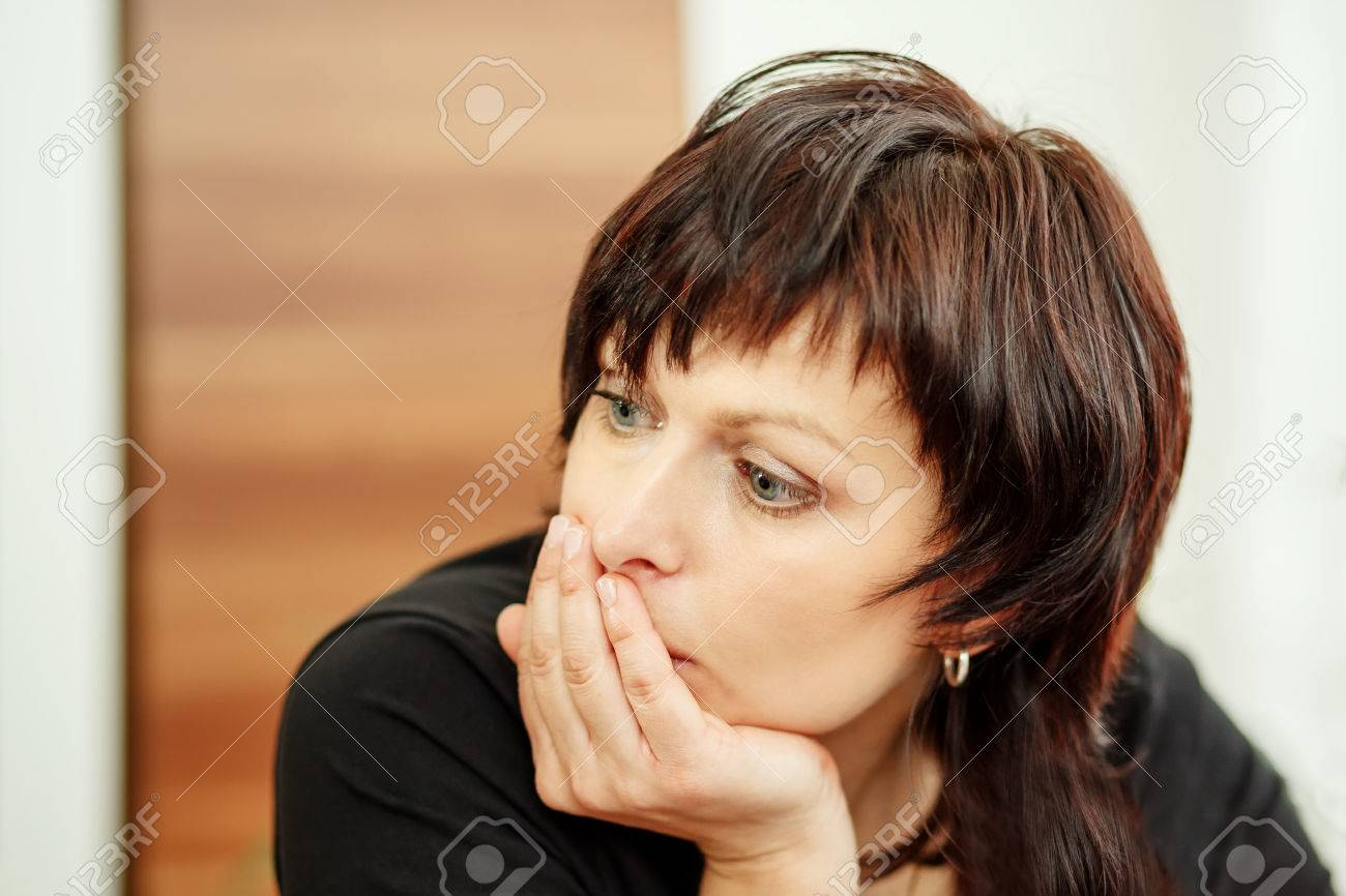 beautiful middle age tired woman holding head, looking out - 28790470