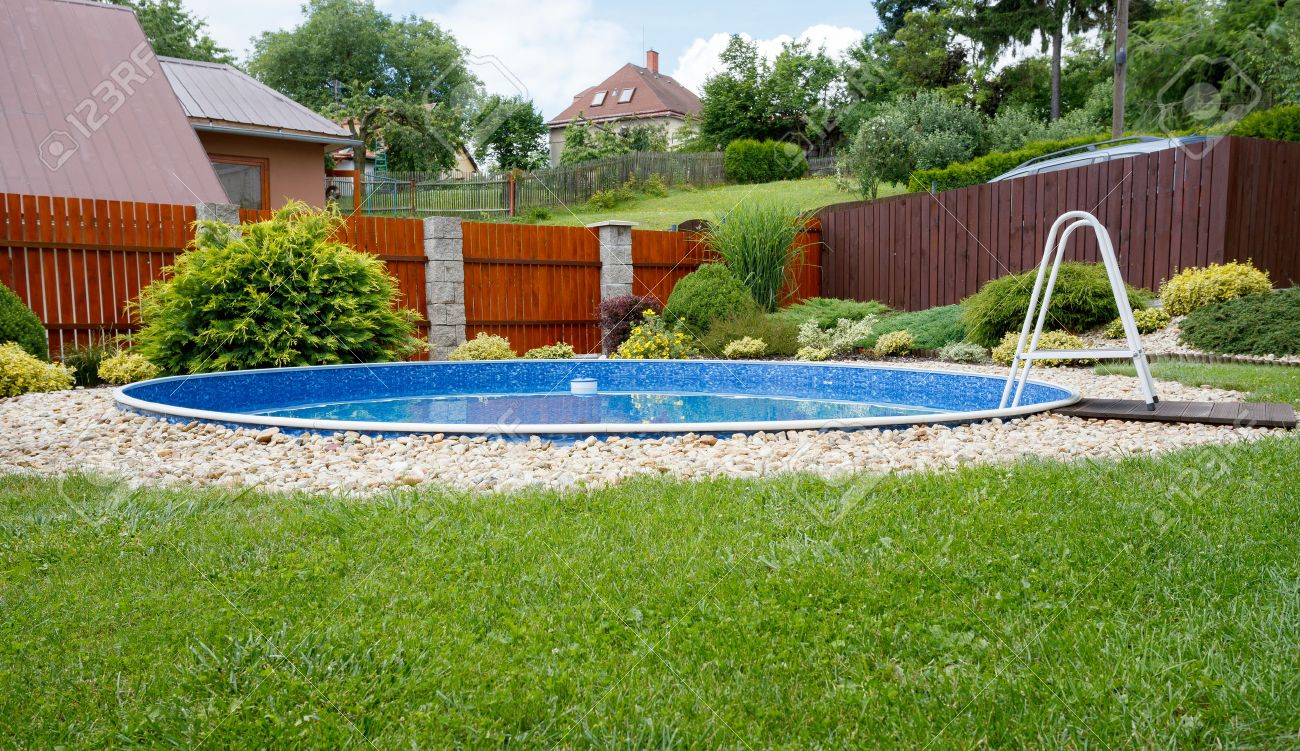 small home swimming pool in rural garden in sunny day stock photo