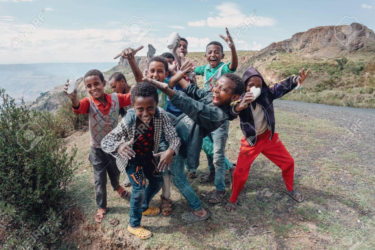 OROMIA REGION, ETHIOPIA, APRIL 19.2019, Group of happy Ethiopian teenager boys on road posing to tourists for photo. Oromia Region, Ethiopia, April 19. 2019 - 128137767