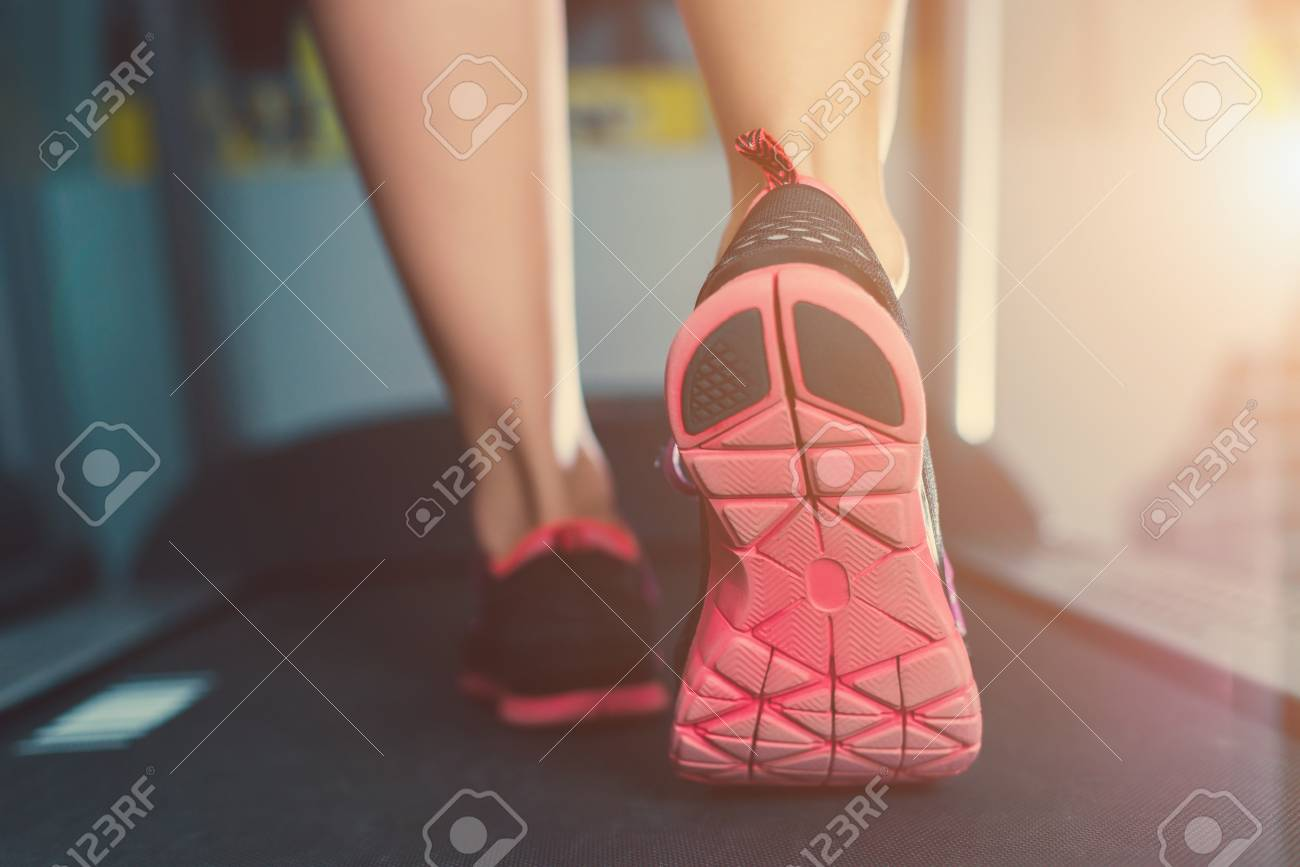 Female Muscular Feet In Sneakers Running On The Treadmill At Stock