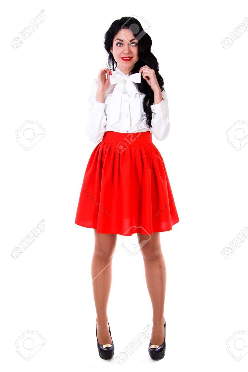 de67eb57ac3596 Mooie jonge vrouw in een witte blouse en een korte rode rok geïsoleerd over witte  achtergrond
