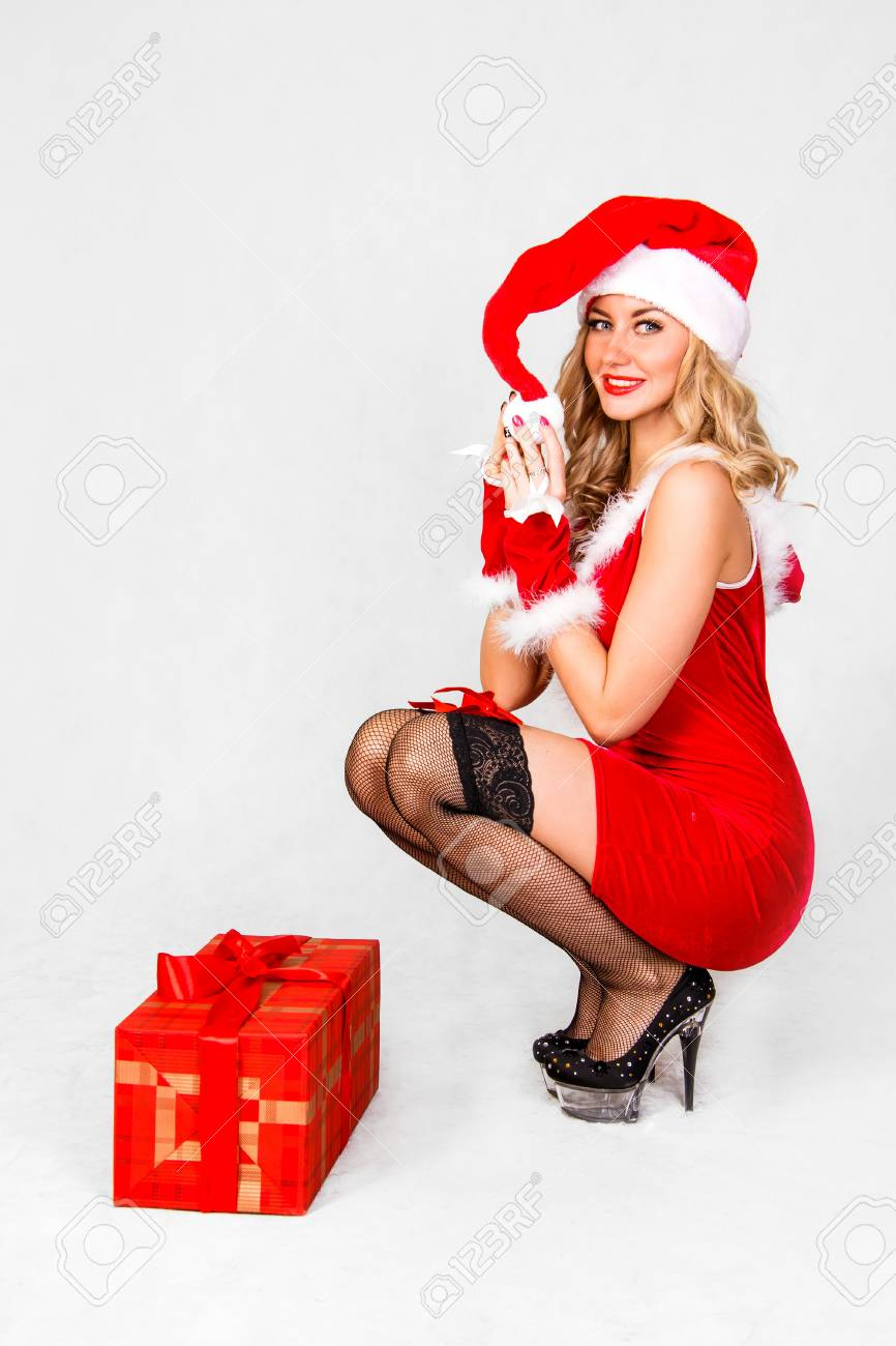 e386039105ea Beautiful young woman in a Christmas clothes over grey background Stock  Photo - 49697593