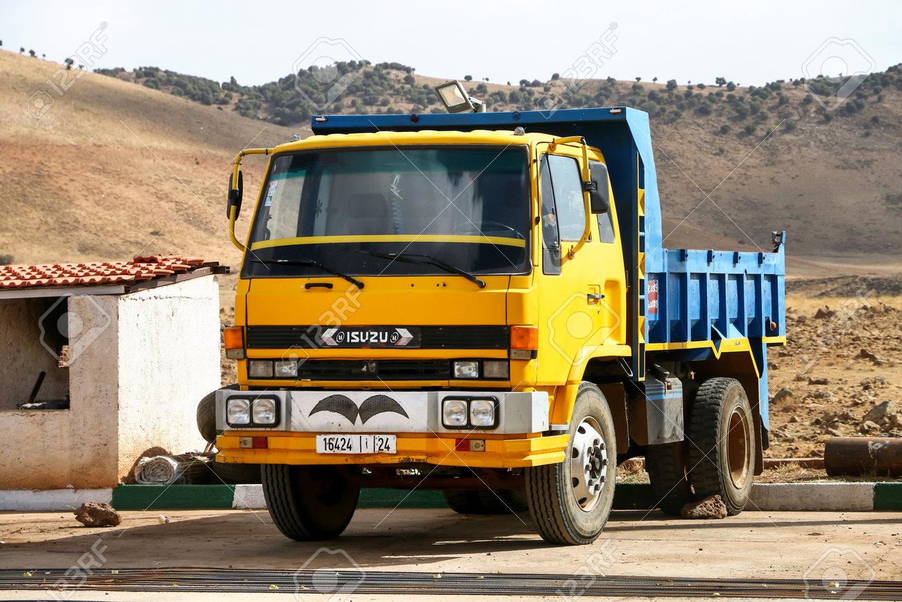 Khenifra Province, Morocco - September 27, 2019: Yellow dump truck Isuzu Forward in the village street. - 137984268