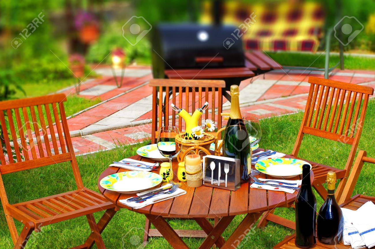 outdoor dining scene in backyard bbq grill in background tilt