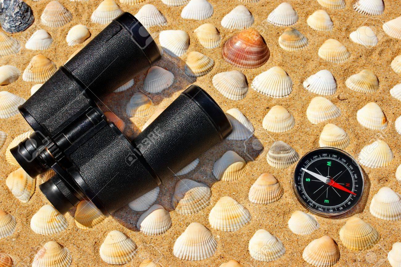 Vintage fernglas kompass und muscheln am strand sand close up