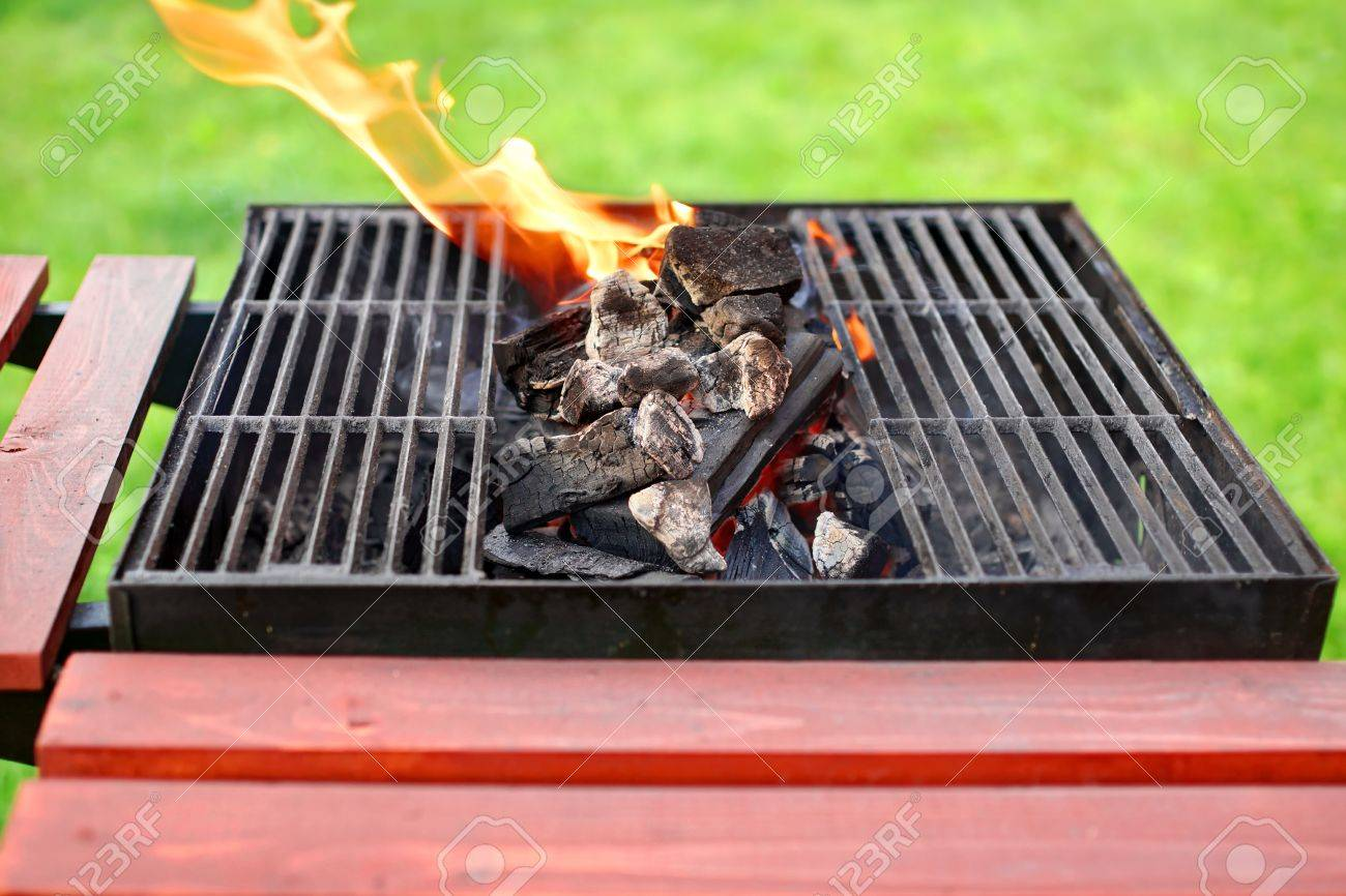 flaming bbq grill backyard lawn in background stock photo