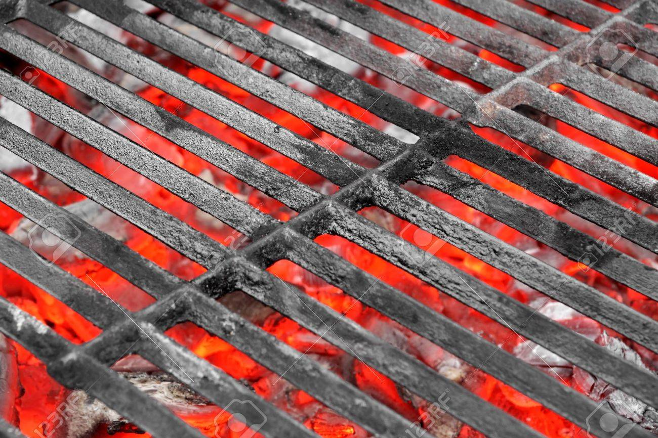 empty black cast iron grill and hot red glowing coals background with space for text
