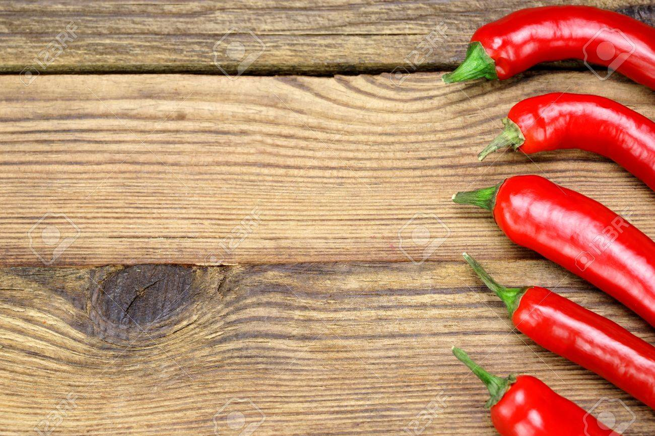 Kitchen Table Background fresh red hot chili peppers on the rustic wood kitchen table