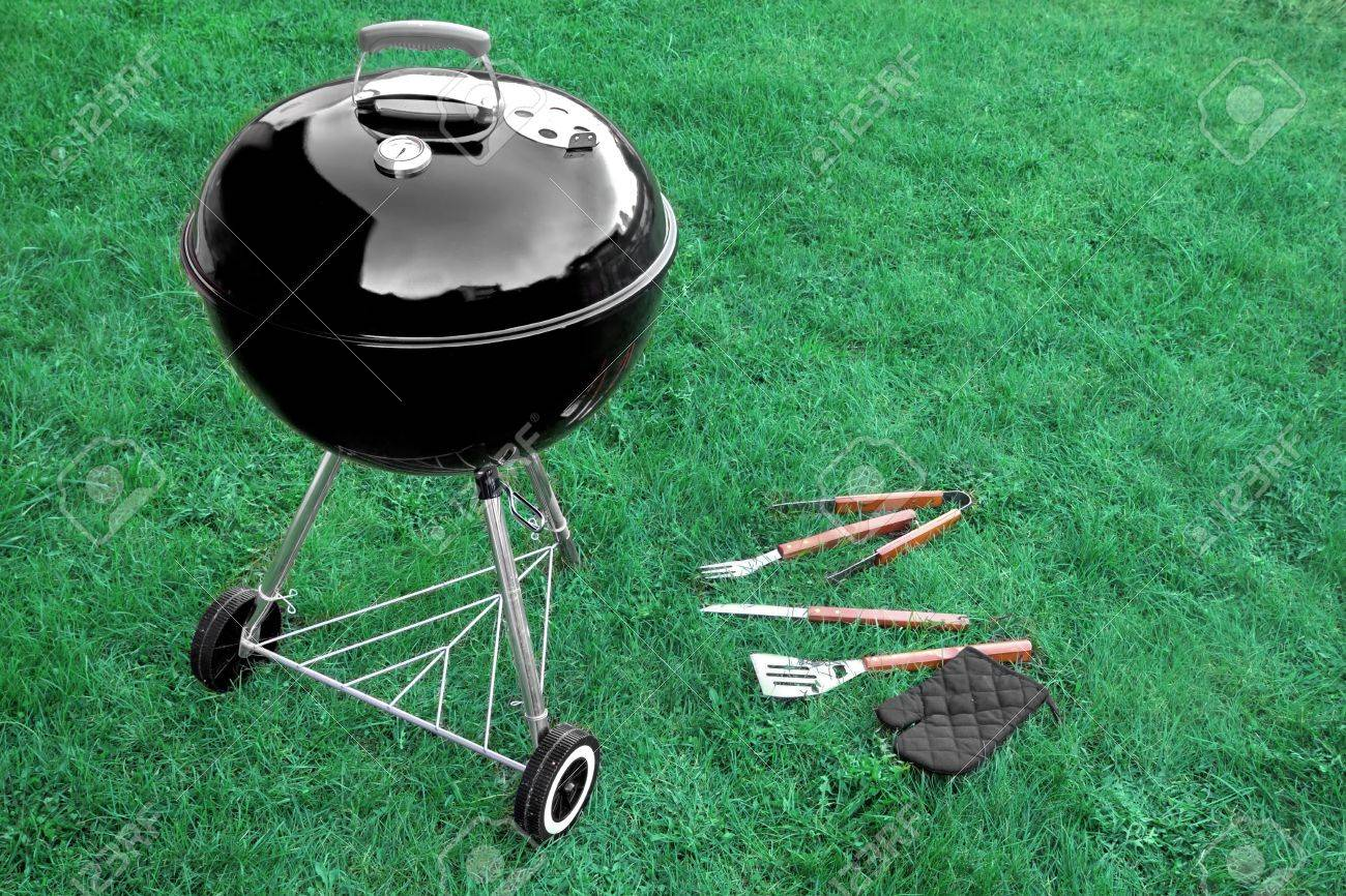 bbq appliance on the lawn with grill tools on the backyard or