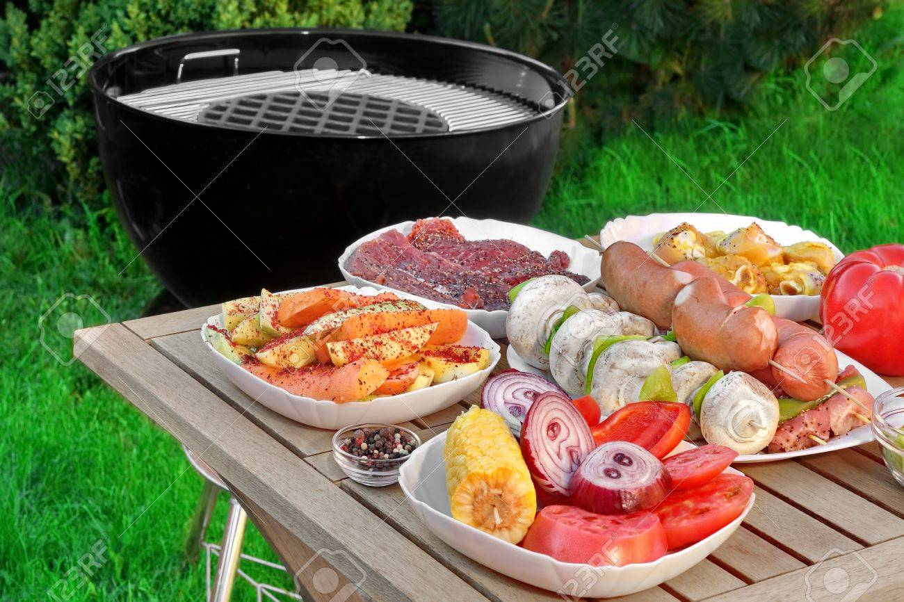 close up view on wood picnic table with different cookout food