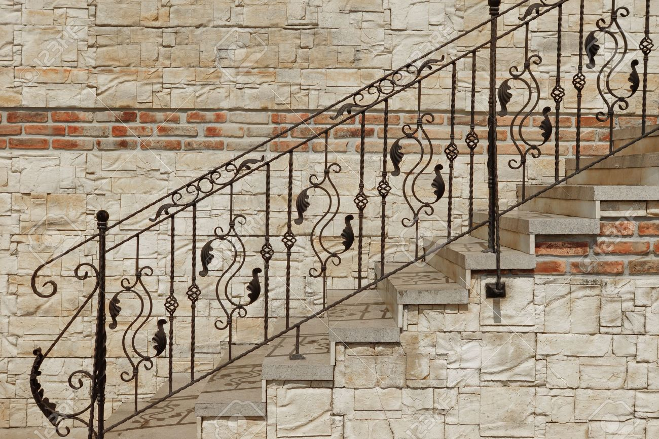 decorative railings. decorative railings: modern vintage style straight stone staircase with black wrought iron ornate handrail near railings