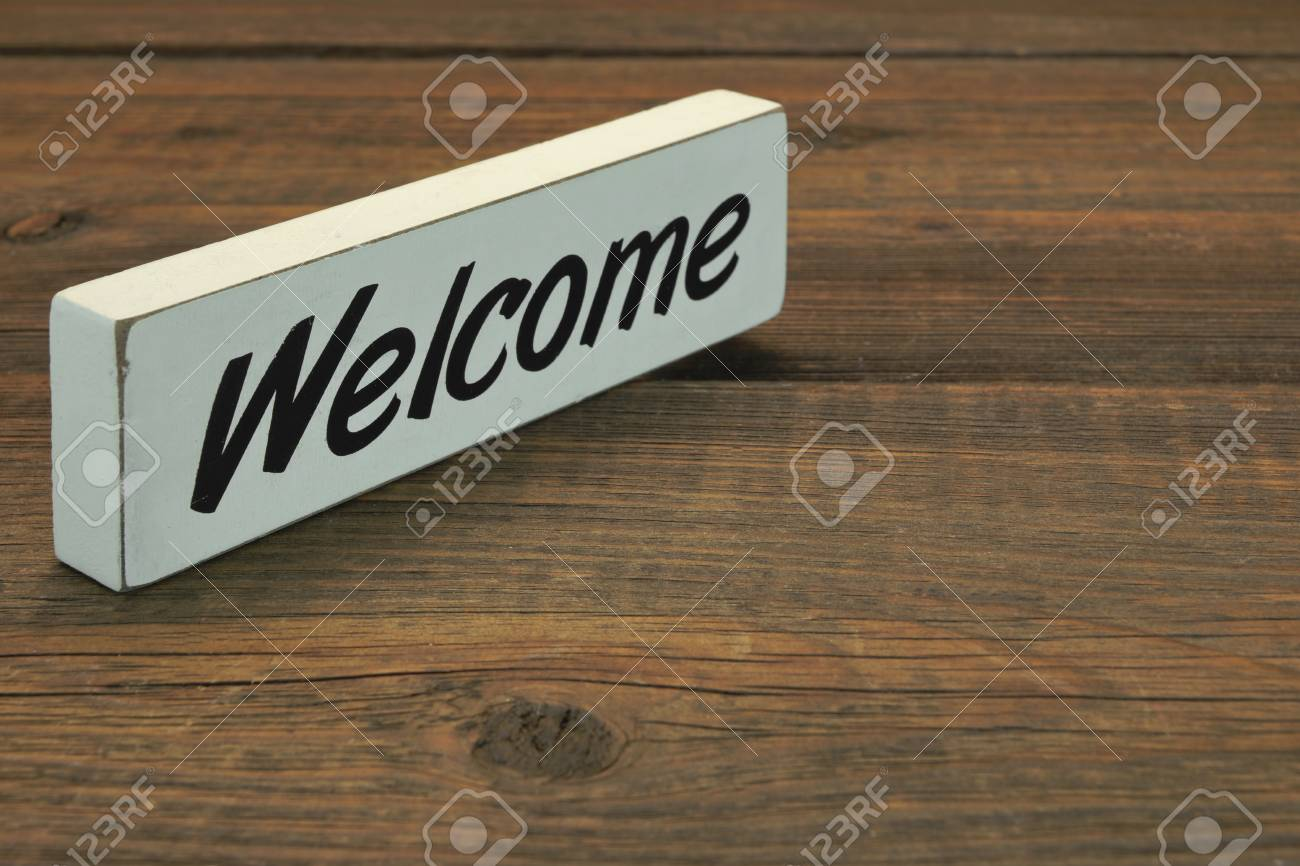 Stock Photo   White Sign Welcome On The Rough Wood Table, Close Up,  Concept, Top View