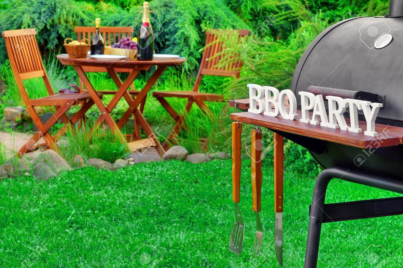 Close Up Of Barbecue Charcoal Grill Appliance With Tools And BBQ Party  Sign, Wooden