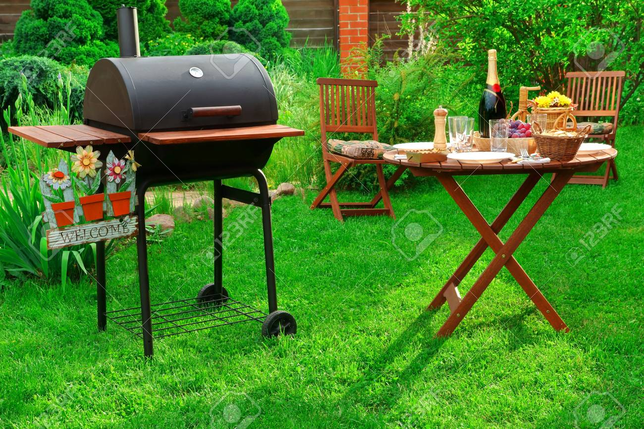 Concept For BBQ Or Picnic Or Party Scene With Charcoal Grill, Served Table  With Bottle