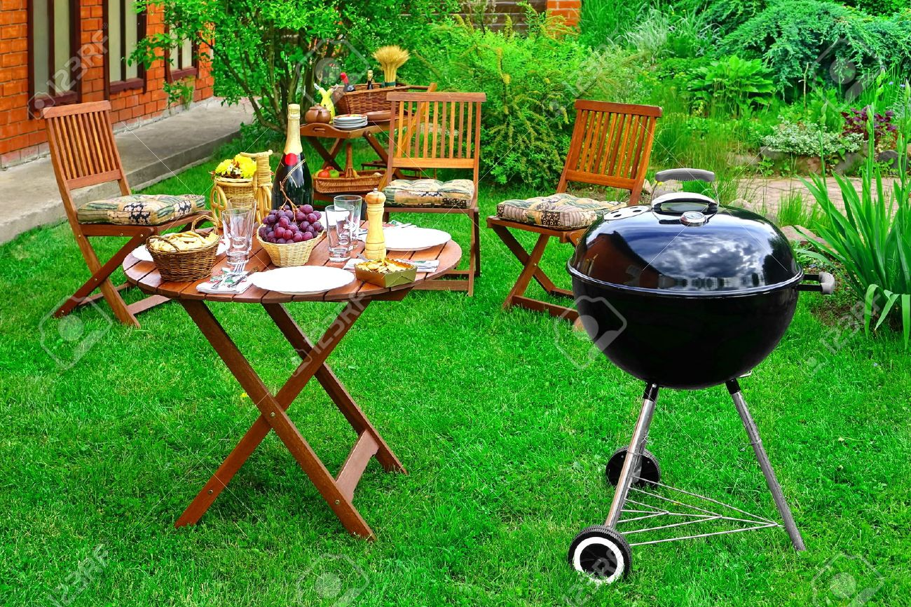 Stock photo summer bbq family party scene in the decorative garden on the backyard charcoal grill appliance wooden chairs and table with appetizers and