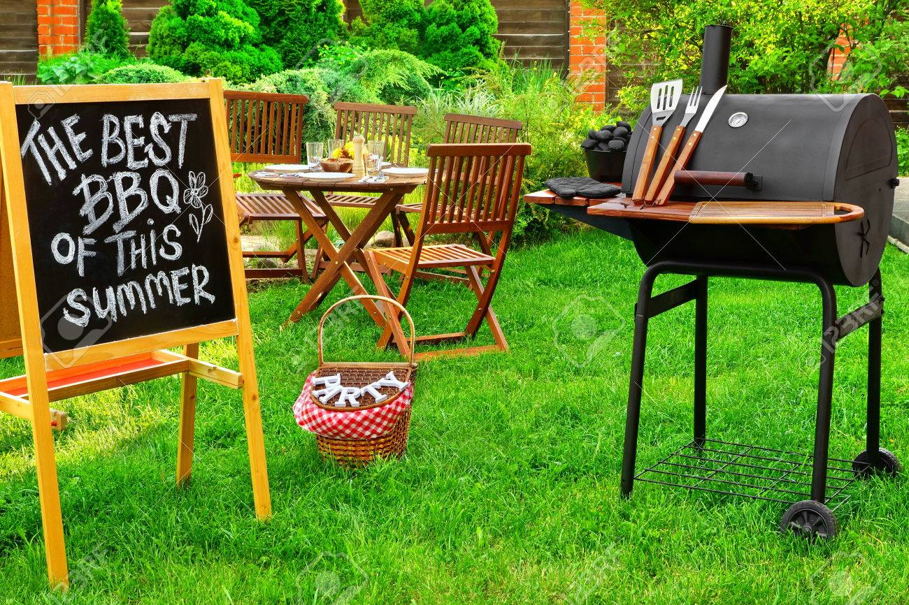 An invitation to a summer barbecue grill party written on blackboard barbecue charcoal grill