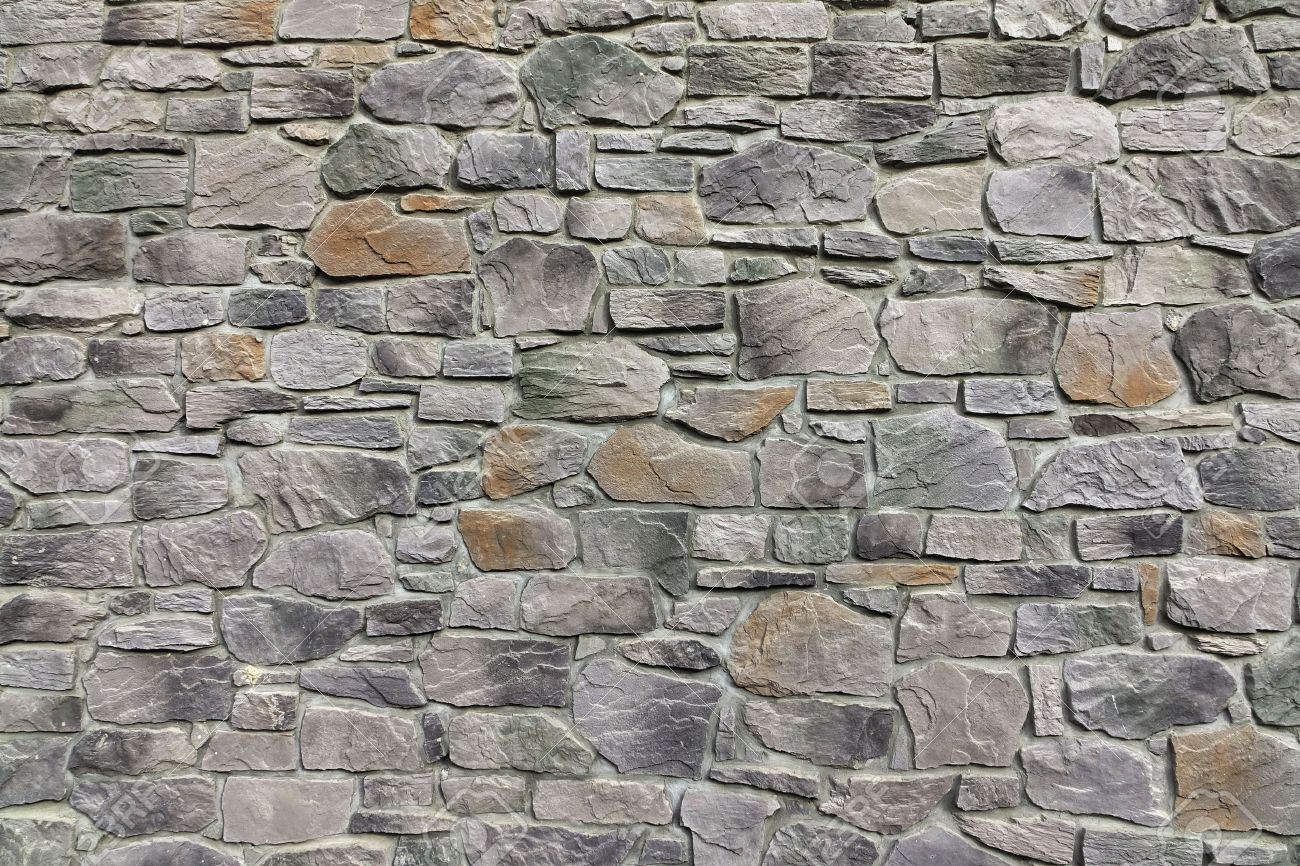modern textured grey yellow stonewall made from flagstone and