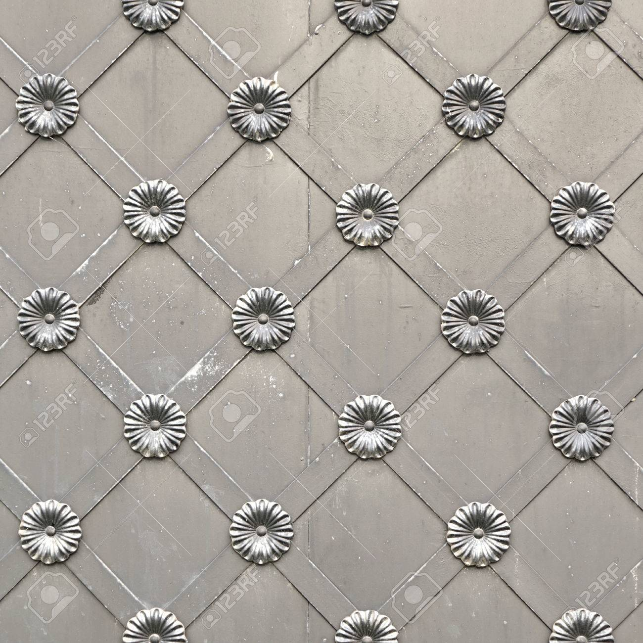 old silver metal gate or door with iron forged decorative grid ornament square background gray