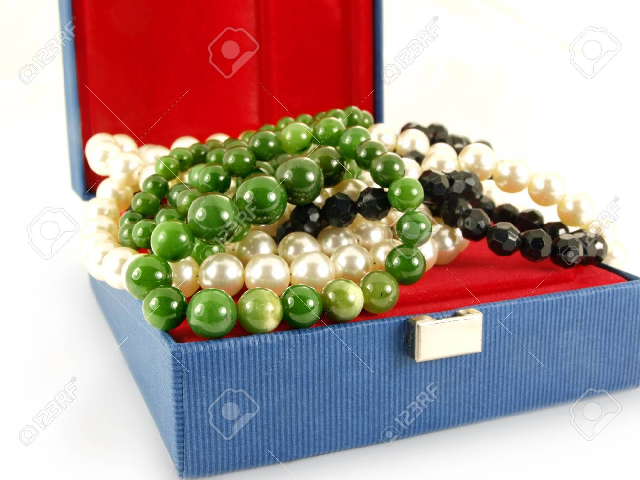 Green emerald gemstone over white and black pearl necklace, in a jewelry box, isolated towards white background Stock Photo - 13040568